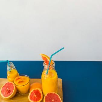 Jugo de toronja con pajita y frutas en tabla de cortar contra el fondo azul