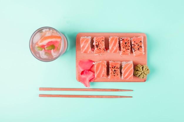 Jugo de toronja con sushi de salmón servido con wasabi y jengibre encurtido sobre fondo de menta