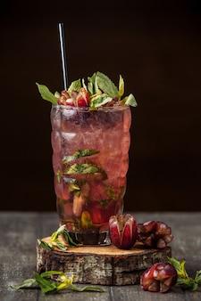 Jugo de uva con rodajas de uva, cubitos de hielo y hojas de menta
