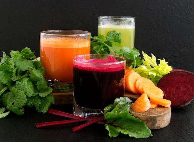 Jugo vegetal en las tazas de cristal en un fondo negro. remolachas, apio, zanahorias.