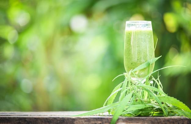 Jugo de verano con batidos de frutas verdes en vidrio con planta de marihuana con hoja de cannabis sobre madera