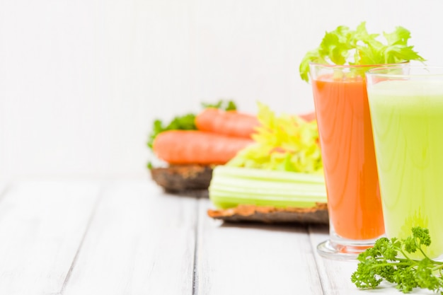 Jugo de zanahoria y apio con verduras frescas en platos de corteza sobre fondo de madera - bebida vegetariana