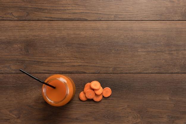 Jugo de zanahoria en un vaso sobre madera