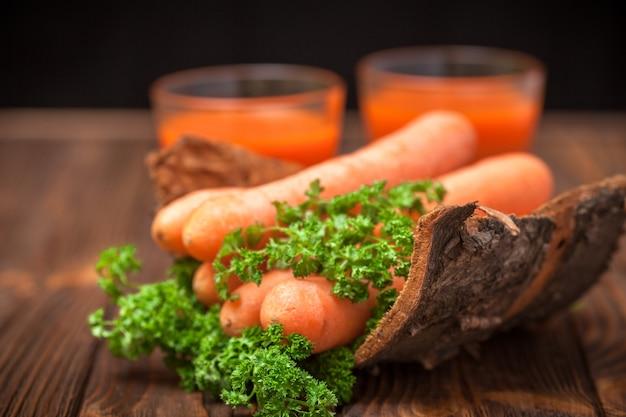 Jugo de zanahoria en vasos hermosos, verduras cortadas de naranja y perejil verde