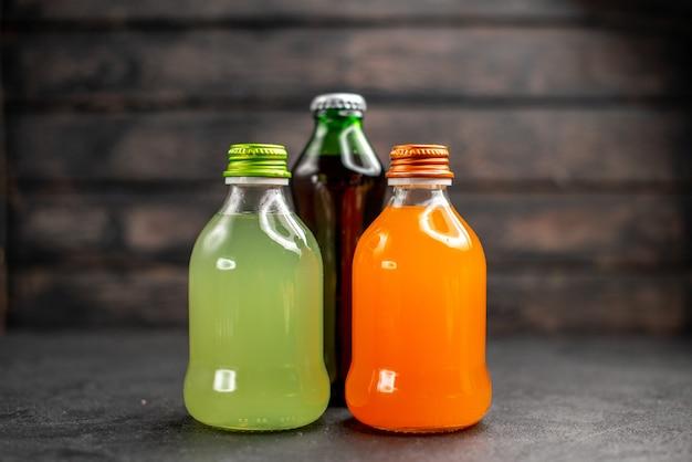 Jugos de vista frontal de diferentes colores en botellas sobre superficie de madera oscura