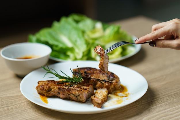 Jugosa carne de cerdo a la parrilla con verduras y especias.