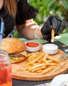 Jugosa hamburguesa con papas fritas ketchup y mayonesa