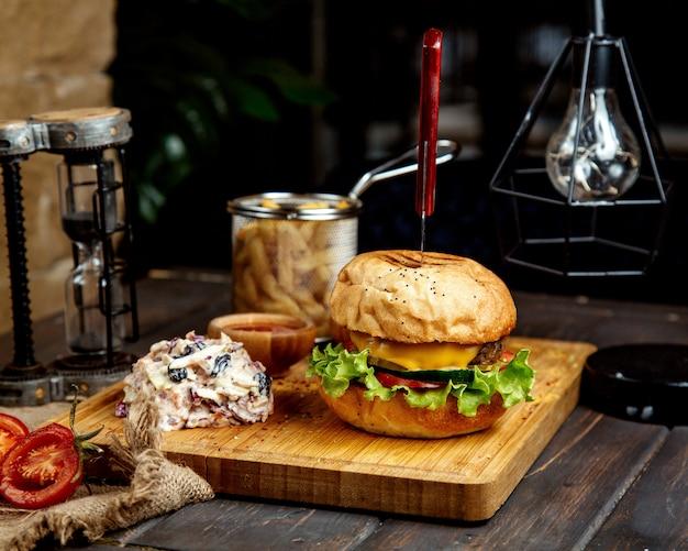 Jugosa hamburguesa con queso con ensalada en una tabla de madera