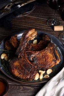 Jugosa, loncha de chuleta de cerdo frita sobre un hueso en aceite con ajo y hierbas en una sartén. de cerca.