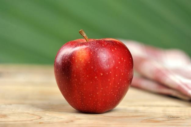 Jugosa manzana roja sobre fondo de madera
