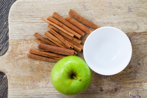 Jugosa manzana verde madura y fragante canela sobre una tabla de cortar de madera, primer plano de alimentos de producción natural cultivados en granjas orgánicas