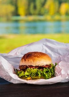 Jugosa sabrosa hamburguesa con carne de res, lechuga, pepinillos, tomate y aros de cebolla en una mesa de madera. comida callejera clásica - hamburguesa a la parrilla