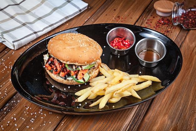Jugosa y sabrosa hamburguesa con pescado y verduras servido en un plato negro con papas fritas. comida rápida americana. hamburguesa de pescado con espacio de copia sobre fondo de madera. de cerca, enfoque selectivo. comida. menú de parrilla