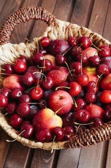 Jugosas cerezas y nectarinas en cesta en mesa de madera.