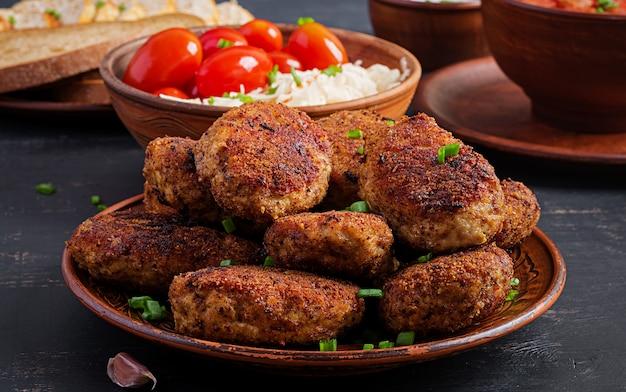 Jugosas chuletas de carne deliciosa en mesa oscura.
