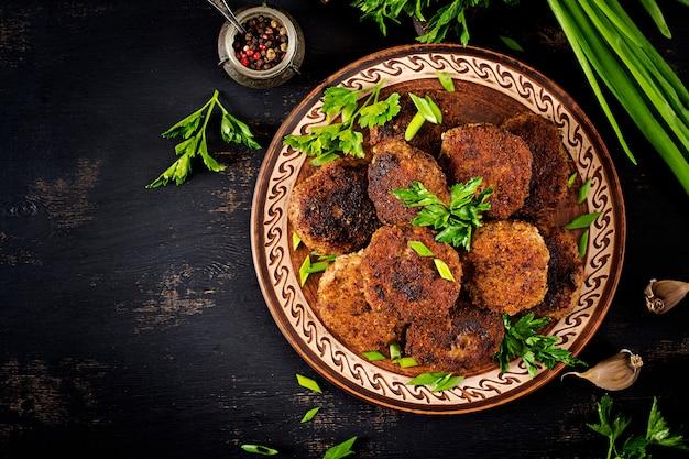 Jugosas chuletas de carne deliciosas en una mesa oscura