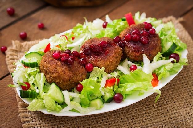 Jugosas chuletas de carne con salsa de arándanos y ensalada en una mesa de madera en un estilo rústico.