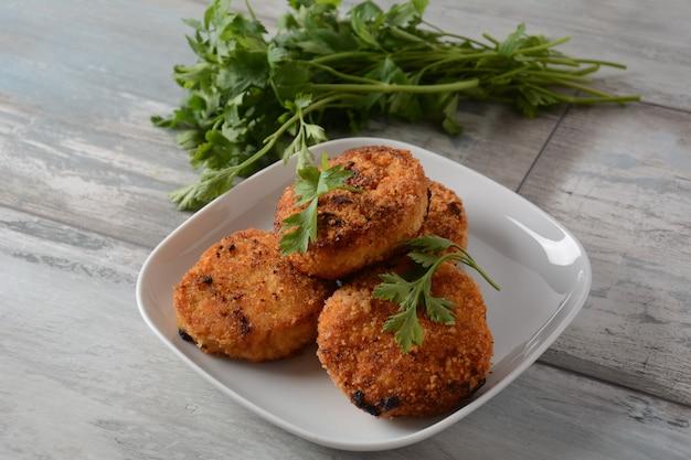 Jugosas chuletas de pollo fritas caseras. rebozado con pan rallado, delicioso, en plato blanco con hierbas. sobre fondo de madera vieja, estilo rústico