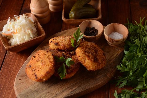 Jugosas chuletas de pollo fritas caseras. revestido con pan rallado, delicioso, sobre tabla de madera oscura vieja, estilo rústico, con especias y hierbas.