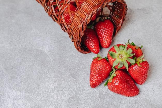 Jugosas fresas cayeron caóticamente sobre un muro de hormigón. deliciosas frutas en temporada de verano. productos naturales y recursos naturales.