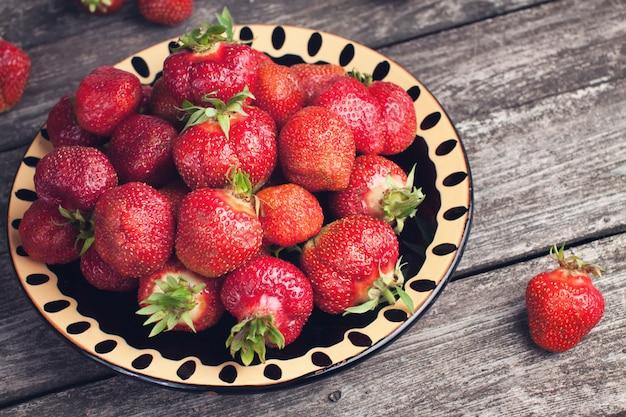 Jugosas fresas en la mesa de madera oscura