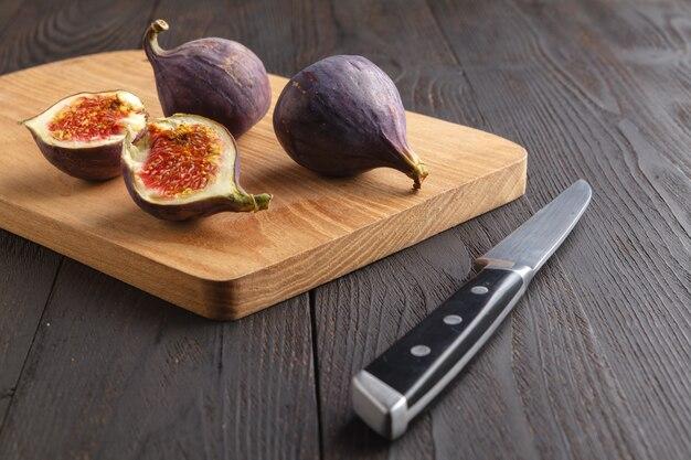 Jugosas frutas frescas de higo entero e higos cortados en una tabla de cortar de madera sobre fondo oscuro
