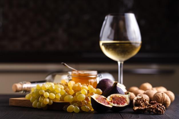Jugosas frutas frescas de higos enteros y un corte de higos y un tazón de miel en panales sobre tabla de cortar de madera