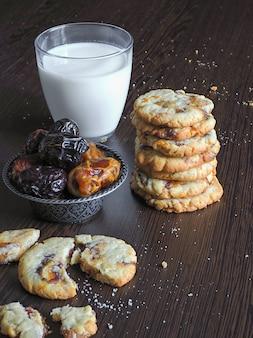 Jugosas galletas de fecha con leche sobre una superficie de madera oscura