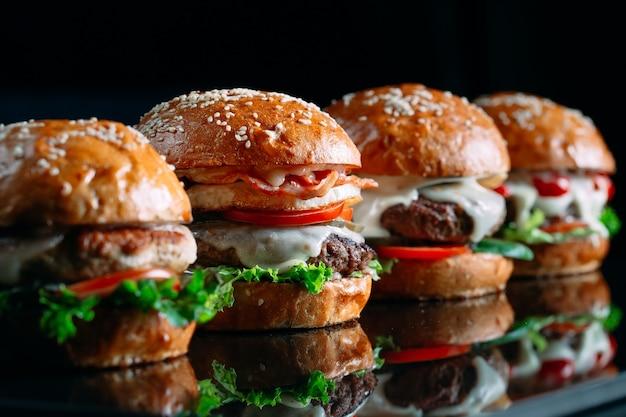 Jugosas hamburguesas de carne sobre un fondo negro.