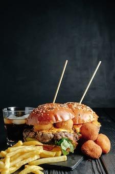 Jugosas hamburguesas caseras sobre tabla de madera, bolas de queso. comida callejera, comida rápida. con papas fritas y vaso de cola.