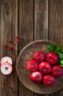 Jugosas manzanas rojas en un cuenco de madera rústico vintage