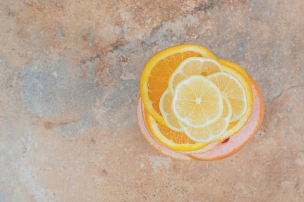 Jugosas rodajas de limón, naranja y pomelo sobre fondo de mármol.