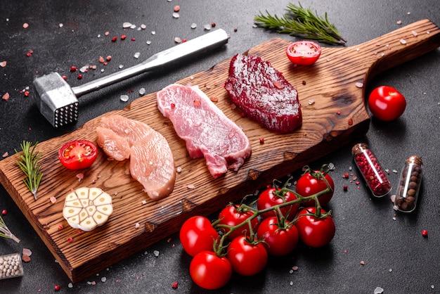 Jugoso bistec de carne de res, cerdo y pollo con verduras listas para cocinar. filetes de diferentes variedades de carne preparada para cocinar.