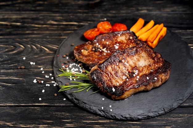 El jugoso pedazo de carne frita se encuentra en una placa de piedra contra una mesa de madera negra