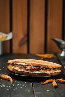 Jugoso sandwich de rabo de buey sobre una mesa de madera oscura
