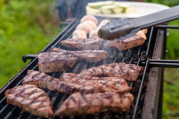 Jugosos filetes de ternera veteada y mitades de champiñón se fríen en una parrilla de carbón.