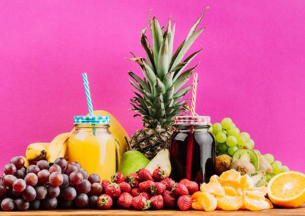 Jugosos frutos coloridos y jugos tarros de albañil contra fondo rosa