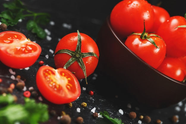 Jugosos tomates cherry rojos con especias, sal gruesa y verduras. tomates dulces y maduros para ensaladas y como ingredientes para cocinar