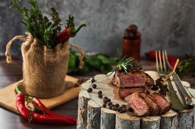 Jugosos trozos medianos de filete de res en una sartén sobre una tabla de madera con un tenedor y un cuchillo