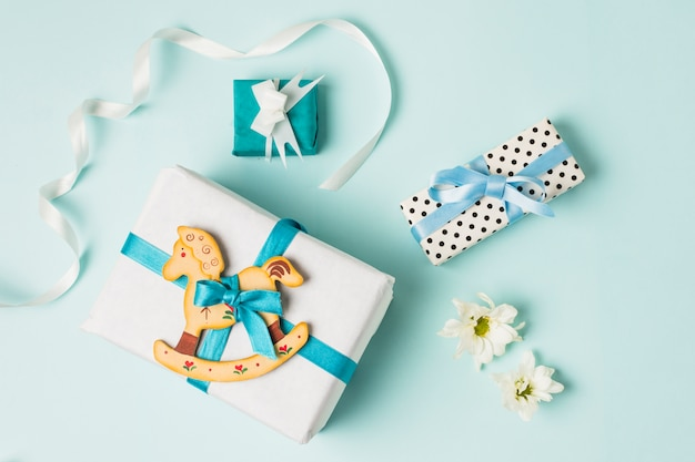 Juguete de caballito con cajas de regalo; flores y cinta sobre fondo azul