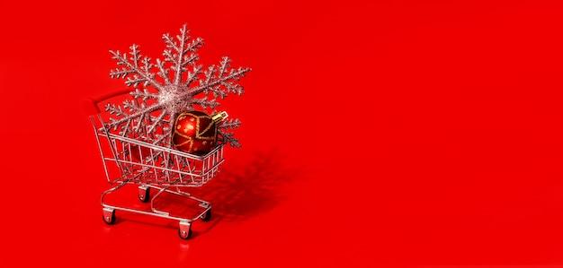 Juguete de carro de compras con juguetes de navidad y pared roja. copie el espacio. descuentos, rebajas. venta de navidad y año nuevo.