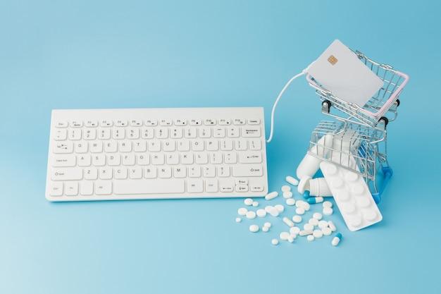 Juguete de carro de compras con medicamentos y teclado. pastillas, blister, frascos médicos, termómetro, máscara protectora sobre un fondo azul. vista superior con lugar para su texto
