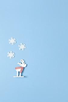 Juguete ciervo blanco en bufanda a cuadros tres pequeños copos de nieve de fieltro en azul pastel.