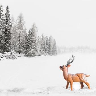 Juguete de ciervo entre campo con árboles en la nieve.