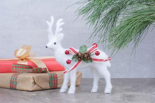 Juguete de ciervo de navidad con caja de regalo festiva.