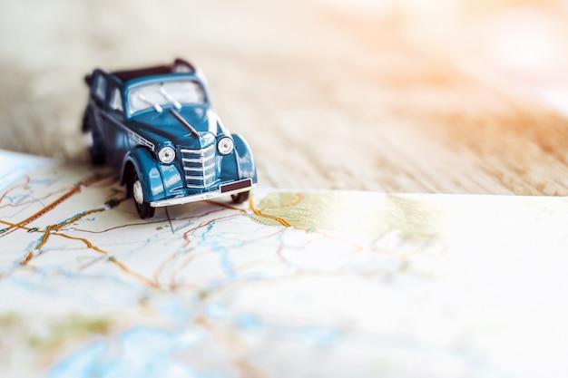 Juguete coche retro cabrio en el mapa, concepto de turismo