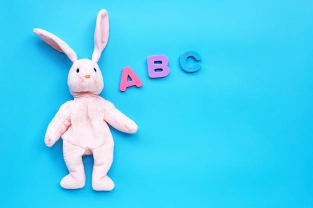 Juguete de conejo con alfabeto inglés sobre fondo azul. concepto de educación