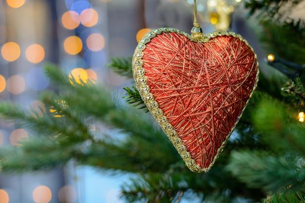 Juguete corazón rojo colgando en el árbol de navidad