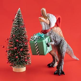 Juguete de dinosaurio con regalo y árbol.