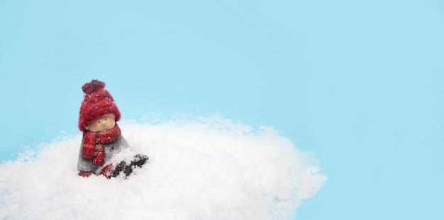 Juguete de duende navideño se sienta en la nieve, banner para encabezado de sitio web